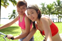 Two women on bicycles, looking at camera - Alex Microstock02