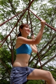 Woman holding on to rope on a jungle gym - Alex Microstock02