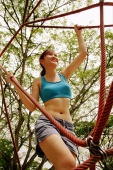 Woman holding on to rope on a jungle gym, low angle view - Alex Microstock02