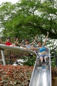 Group of young people sliding down playground slide - Alex Microstock02