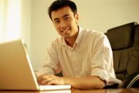 Executive using laptop, looking at camera - Alex Microstock02