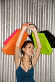 Young woman carrying shopping bags over her head, smiling at camera - Alex Microstock02
