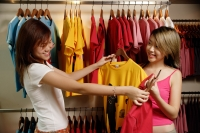 Young women at clothes shop looking at T shirts - Alex Microstock02