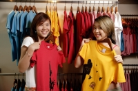 Young women at clothes shop holding up T shirts - Alex Microstock02