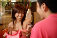 Young woman passing store clerk her credit card - Alex Microstock02