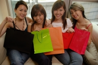 Young women sitting on sofa, side by side, holding shopping bags - Alex Microstock02