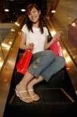 Young woman sitting escalator holding shopping bags - Alex Microstock02