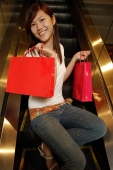 Young woman sitting escalator holding shopping bags, looking at camera - Alex Microstock02
