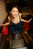 Young woman on escalator holding shopping bags, looking up at camera - Alex Microstock02