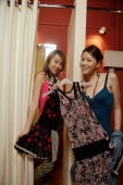 Two women trying on clothes at shop, looking at camera - Alex Microstock02