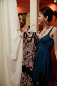 Two women trying on clothes at shop, one behind curtain - Alex Microstock02