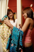 Two women trying on clothes at shop, one inside fitting room - Alex Microstock02