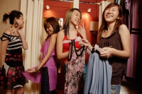 Four young women at shop, looking at and trying on clothes - Alex Microstock02