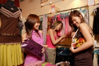 Young women at shop, looking at clothes and bags - Alex Microstock02
