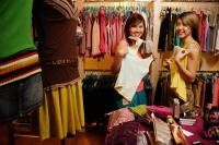 Two young women at clothes shop, holding up clothes, looking at camera - Alex Microstock02