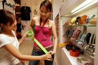 Two young women looking at belts in shop - Alex Microstock02