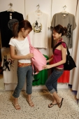 Two young women looking at bags in shop - Alex Microstock02