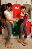 Two young women looking at bag in shop - Alex Microstock02