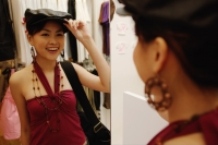 Young woman trying on beret, looking in mirror - Alex Microstock02