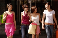 Four young women, walking side by side, carrying shopping bags - Alex Microstock02