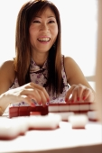 Woman playing mahjong, smiling - Alex Microstock02