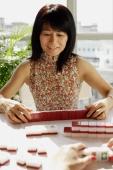 Woman looking at mahjong tiles - Alex Microstock02