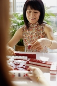 Woman holding mahjong tile - Alex Microstock02