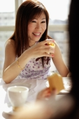 Woman holding cake slice, facing another woman - Alex Microstock02