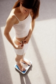 Young woman on weighing scale looking down at tape measure around her waist - Alex Microstock02