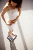 Young woman on weighing scale holding a tape measure around her waist - Alex Microstock02