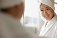 Young woman looking at mirror, towel wrapped around her head - Alex Microstock02