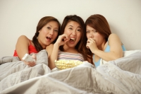 Young women lying on bed side by side, eating popcorn - Alex Microstock02