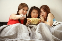 Young women lying on bed watching TV - Alex Microstock02