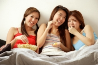 Young women sitting side by side, eating popcorn and watching TV - Alex Microstock02