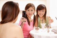 Young women holding camera phone, photo messaging - Alex Microstock02