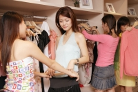 Young women looking through clothes rack at shop - Alex Microstock02