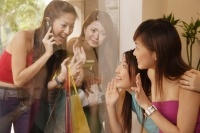 Young women looking at each other through glass window - Alex Microstock02
