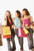 Three young women with shopping bags, walking side by side, one on the phone - Alex Microstock02