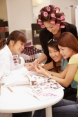 Young women at a beauty salon, getting manicure - Alex Microstock02