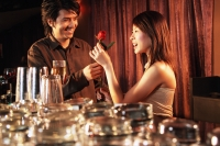 Young man giving young woman a rose at night club - Alex Microstock02