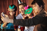 Couples with mask and hat using camera phone to take a picture - Alex Microstock02