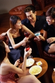 Three young women and a man in entertainment club, holding drinks - Alex Microstock02