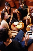 Young people at entertainment club, man holding out credit card for payment - Alex Microstock02