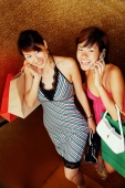 Two women with shopping bags, one on the phone, looking at camera - Alex Microstock02