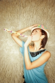 Young woman wearing hat, blowing noisemaker - Alex Microstock02