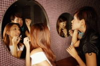 Young women putting on make-up in washroom - Alex Microstock02