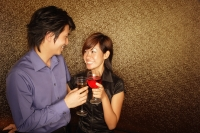 Couple toasting drinks, looking at each other - Alex Microstock02