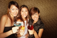 Young women holding drinks, smiling and looking at camera - Alex Microstock02