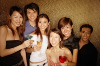 Young adults holding drinks, smiling and looking at camera - Alex Microstock02