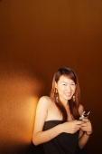 Young woman holding mobile phone, smiling - Alex Microstock02